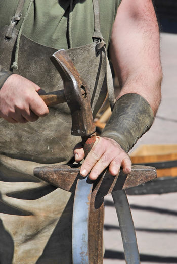 Midsection of blacksmith hammering while standing outdoors