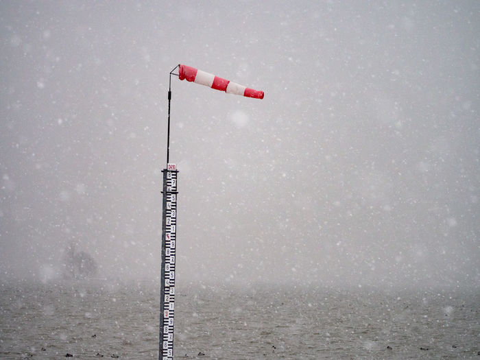Windsock on pole in sea against sky during snowy weather