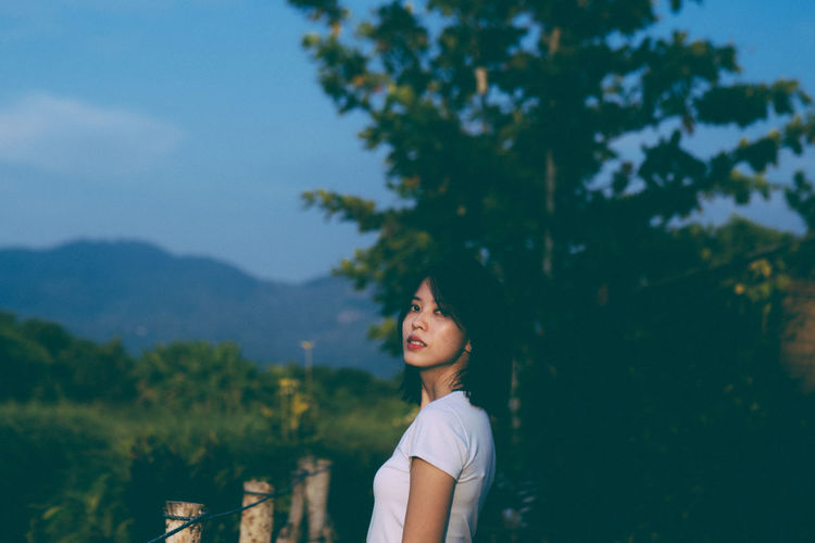Side view of woman standing against trees