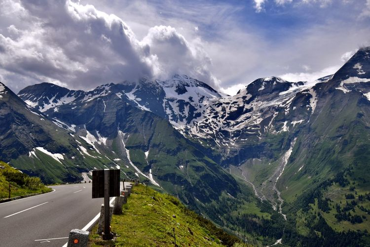 Scenic view of road and snowcapped mountains against sky