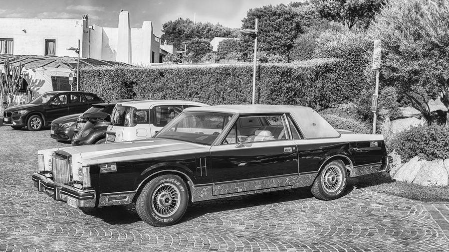 Vintage car on road by buildings in city