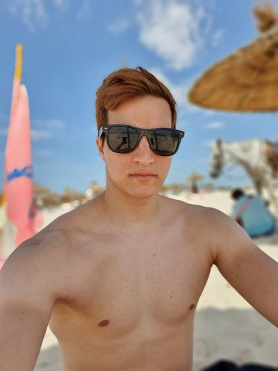 Portrait of young man wearing sunglasses sitting at beach