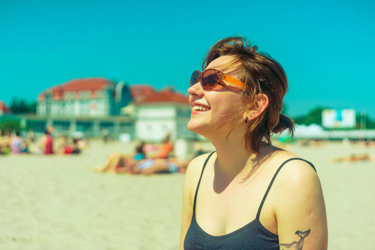 Smiling young woman wearing sunglasses at beach during sunny day