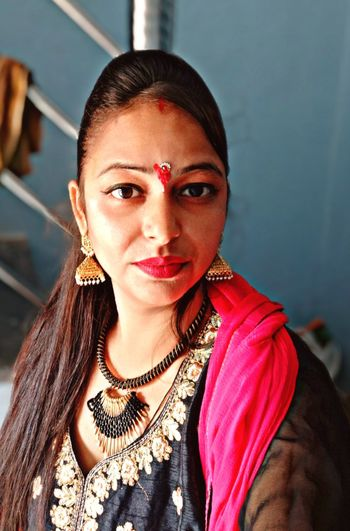 Portrait of young woman wearing traditional clothing and jewelries at home