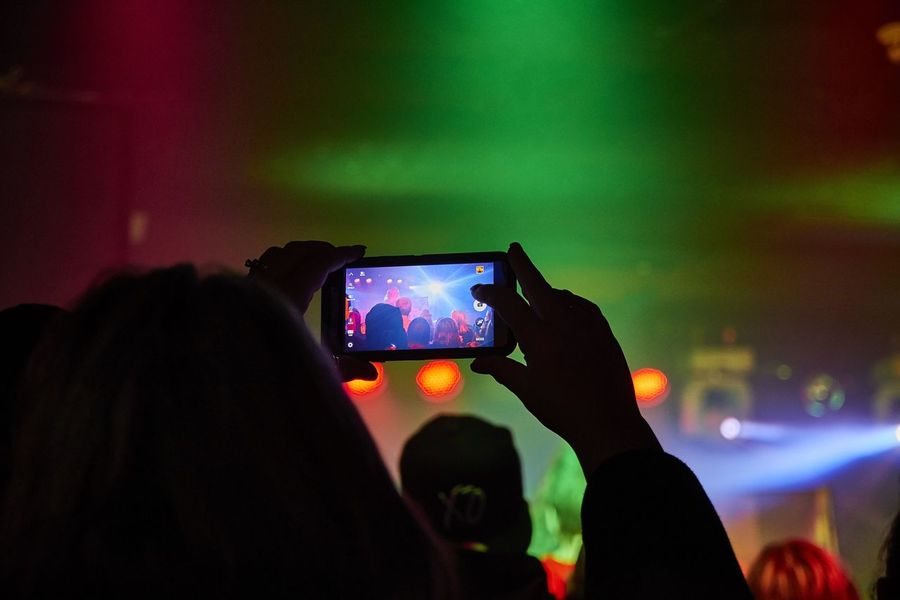 A photo of a fan taking a photo with his or her smartphone at a concert Arts Culture And Entertainment Band Bokeh Concert Concert Photography Depth Of Field Hobbies Illuminated Lighting Equipment Live Music Music Performance Selective Focus Stage Stage Lights Technology