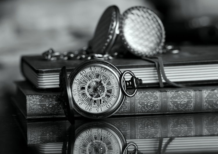 Close-up of pocket watches and books on table
