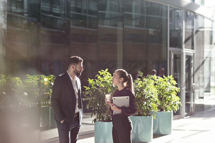 Man and woman standing on mobile phone in city