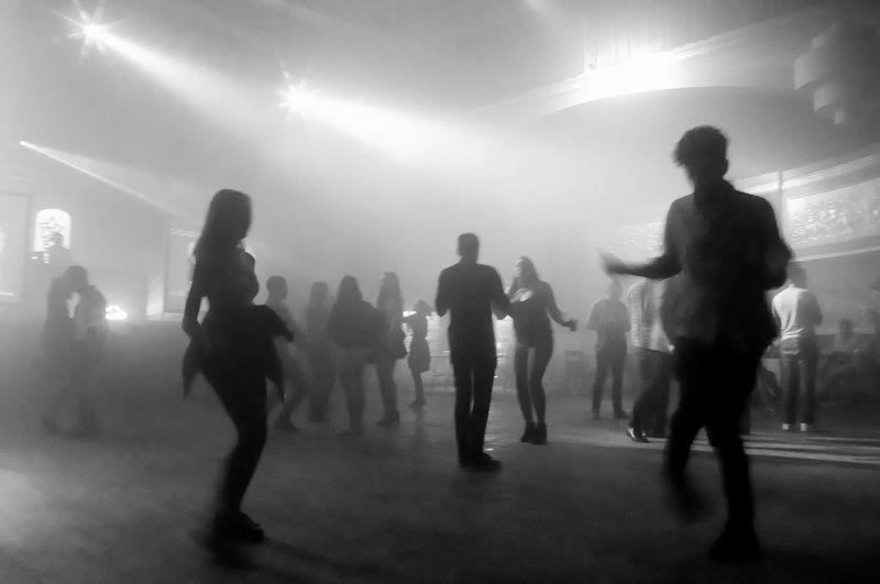 Silhouette people walking on illuminated stage
