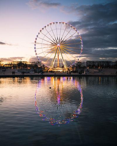 Ferris wheel in illuminated amusement park against sky at sunset