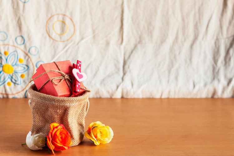 Close-up of artificial flowers and gift in sack on wooden table