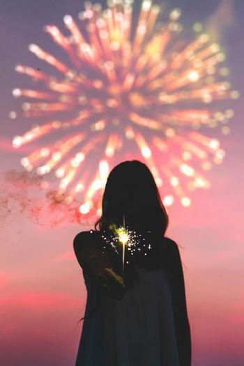 Woman holding illuminated sparkler against dramatic sky at sunset