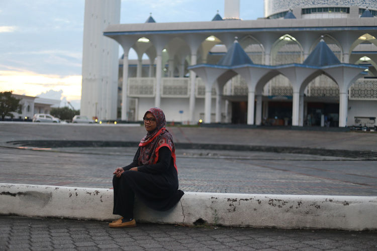 Portrait Of Young Woman Sitting At Roadside Against Mosque In City