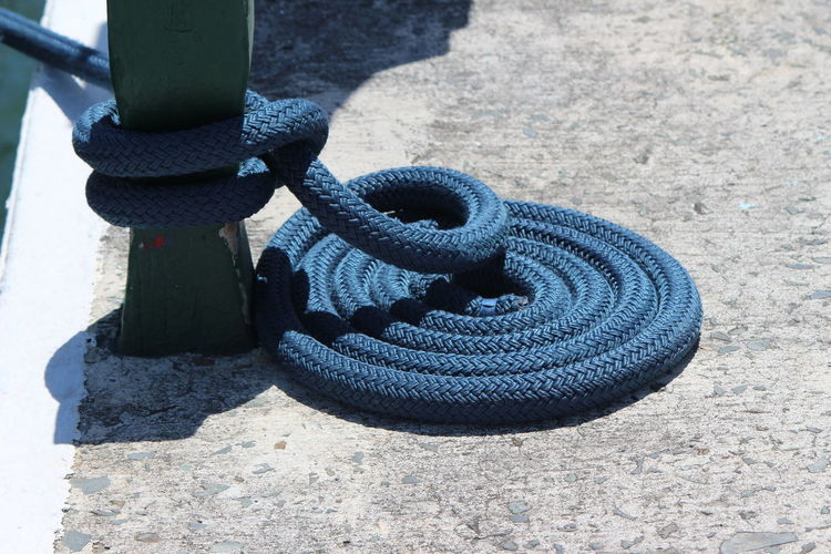 Close-up of mooring rope tied to cleat