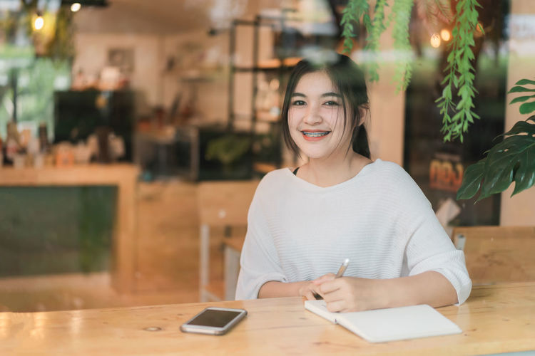 Portrait of smiling young woman using smart phone at table