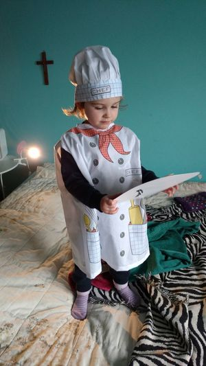Girl in chef costume holding paper while standing on bed