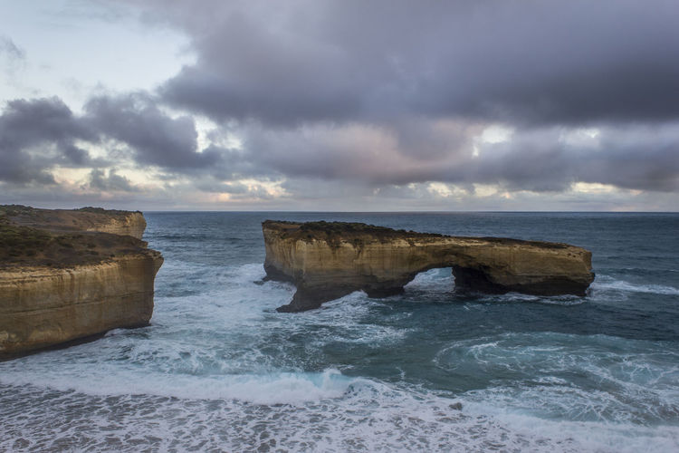 Rock formation in sea at the twelve apostles against cloudy sky