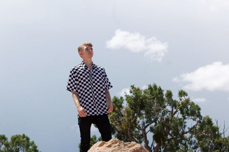 Low Angle View Of Man Wearing Checked Patterned Shirt While Standing Against Sky