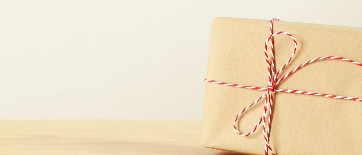 Close-up of paper tied up on white background