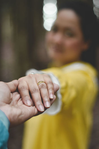 Midsection of couple holding yellow hands