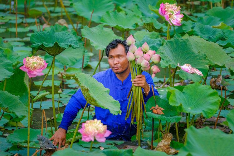 Man holding flowering plants