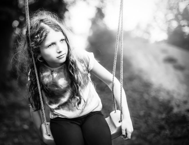 Thoughtful girl sitting on swing at playground