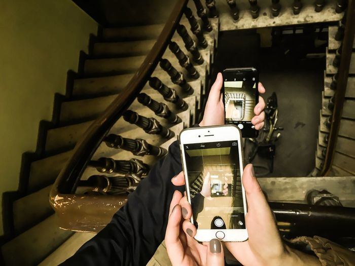 Cropped hand of women photographing staircase with mobile phones