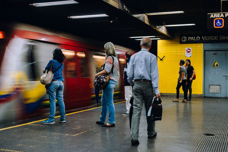 Rear view of people walking on subway station