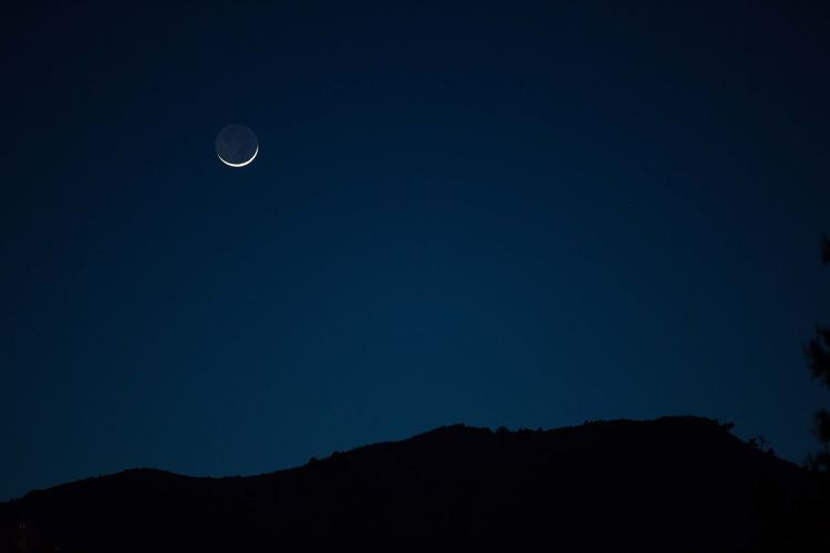 The crescent moon over the mountain foothills. Moon Sky Space Beauty In Nature Night Astronomy Scenics - Nature Tranquil Scene Tranquility Low Angle View Silhouette Nature Crescent No People Mountain Full Moon Blue Copy Space Dark Idyllic Outdoors Planetary Moon Eclipse Moonlight Foothills