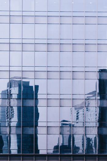Reflection composite image of glass building against sky