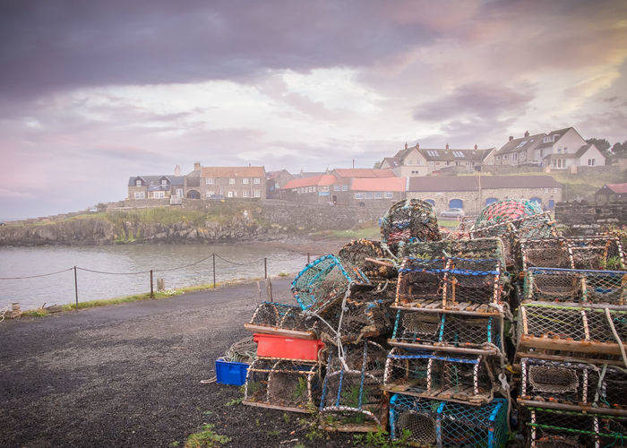 Pile of crab pot on field by river against cloudy sky