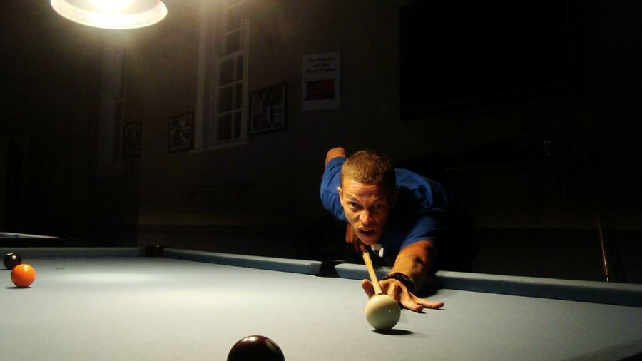 Young man playing pool against wall