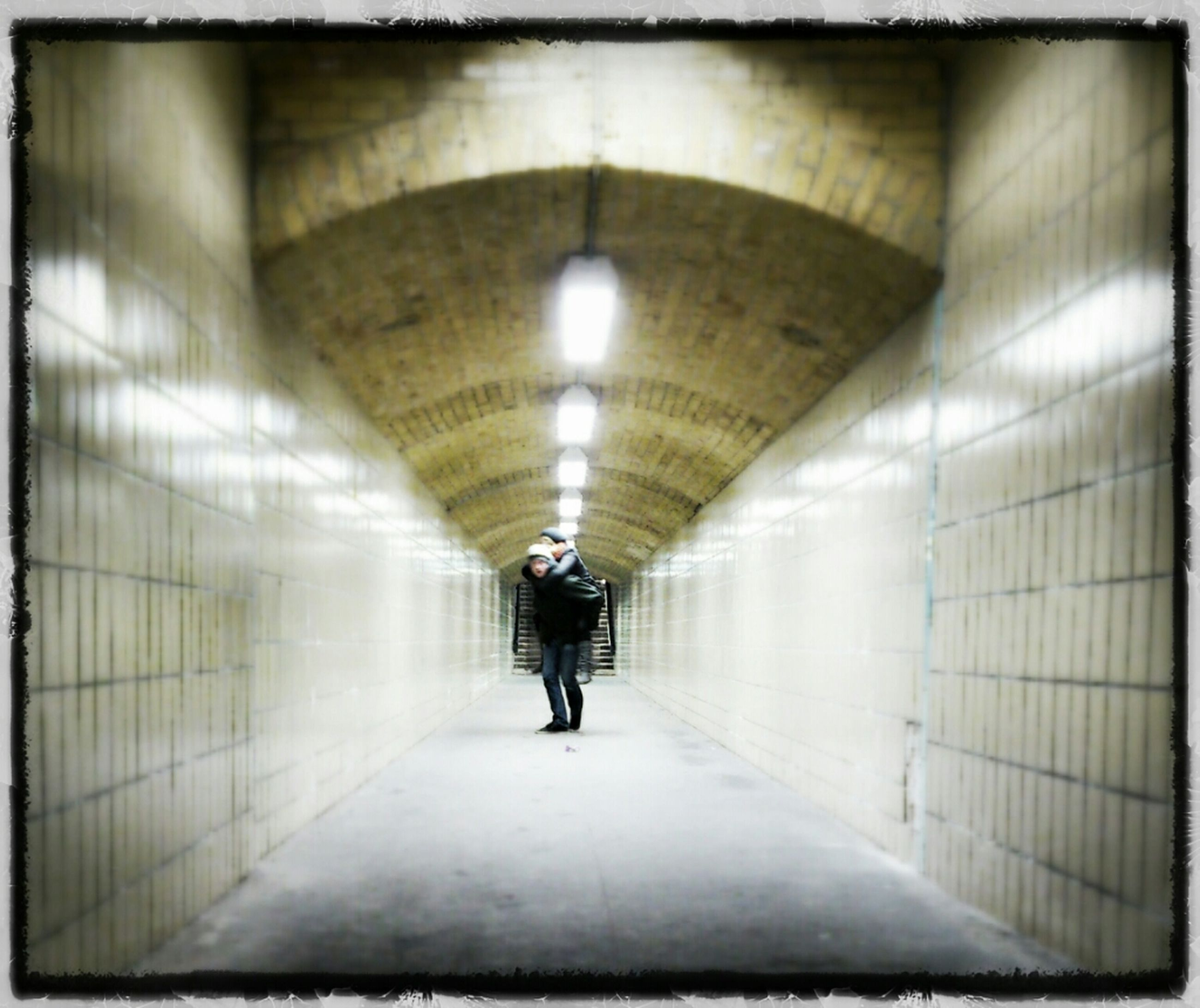 indoors, full length, tunnel, walking, illuminated, ceiling, lifestyles, rear view, men, the way forward, architecture, built structure, lighting equipment, corridor, leisure activity, transportation, arch, diminishing perspective