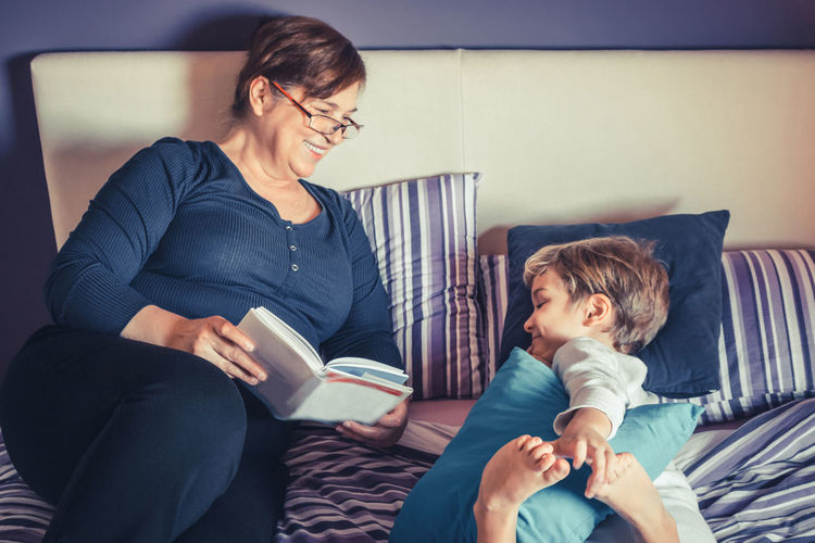 Smiling Grandmother Reading Book For Grandson On Bed