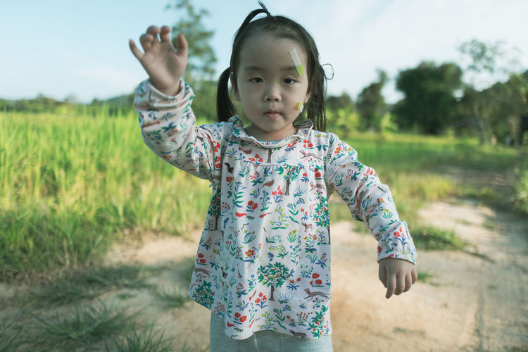 Portrait of cute girl with bandages on face standing on land
