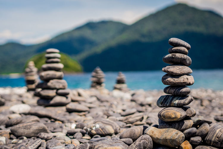Stone stack at lakeshore against mountains