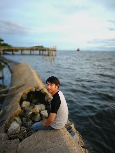 Portrait of young man sitting on broken groyne in sea