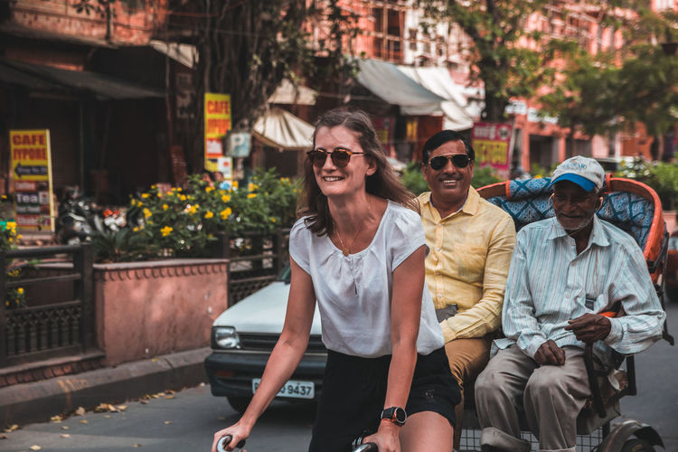a foreign tourist driving a rickshaw, while the owner is sitting back happily ... Real People Three Quarter Length Smiling Sunglasses Men Young Adult Looking At Camera Young Men Casual Clothing Togetherness Glasses Portrait Happiness Adult Front View Lifestyles Fashion Leisure Activity Emotion Sitting Couple - Relationship Outdoors Jaipur Streetphotography Street Rickshaw Activity Cultures Car The Art Of Street Photography The Mobile Photographer - 2019 EyeEm Awards The Traveler - 2019 EyeEm Awards The Street Photographer - 2019 EyeEm Awards
