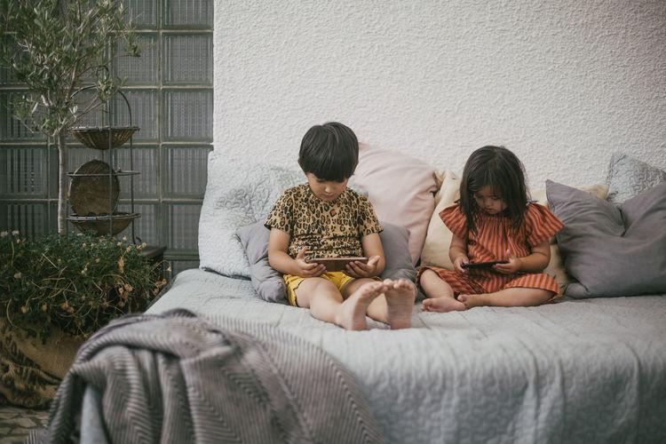 Rear view of friends sitting on floor