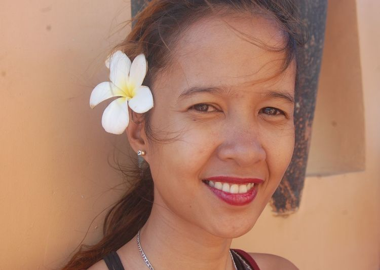 Close-Up Portrait Of Smiling Woman Wearing Flower