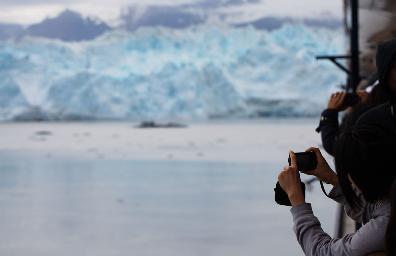 Rear View Of People Photographing Glacier While Standing On Boat