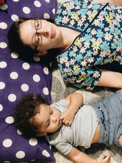 High angle view of baby girl lying on woman