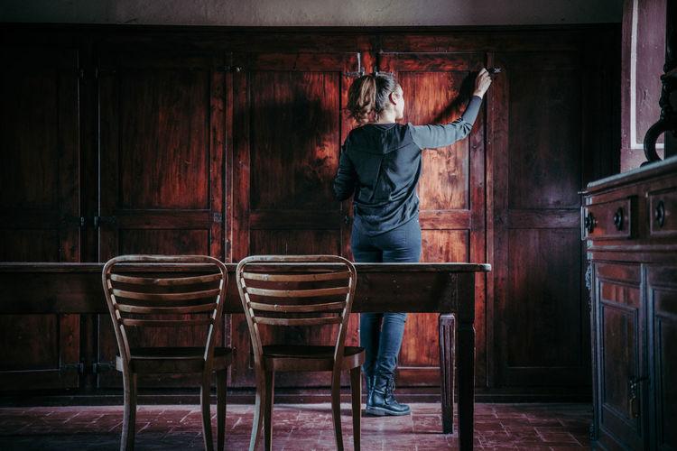 Full length rear view of woman closing door at home