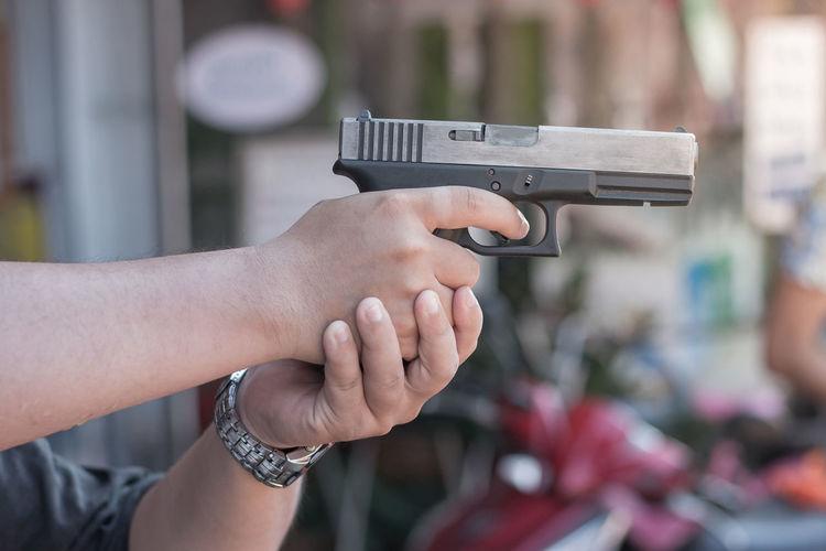 Cropped hand of man holding gun