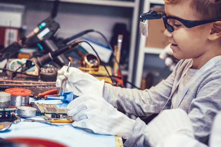 Side view of boy repairing computer par i it workshop.