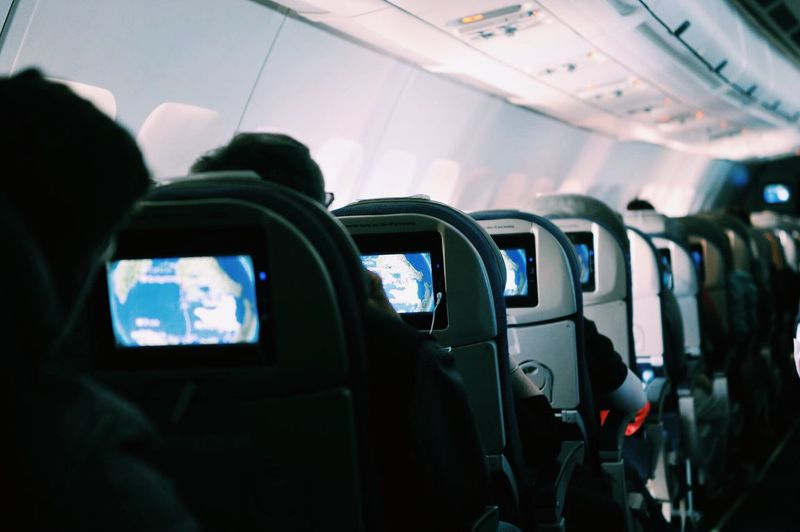 Rear view of people on seats in airplane