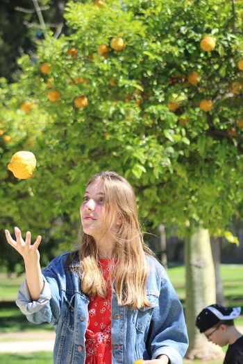 Enjoying the sun Fruit Standing Orange Beautiful Woman Hairstyle Waist Up Casual Clothing Long Hair Blond Hair Lifestyles Women Tree Leisure Activity Hair Real People One Person Springtime Decadence Outdoors