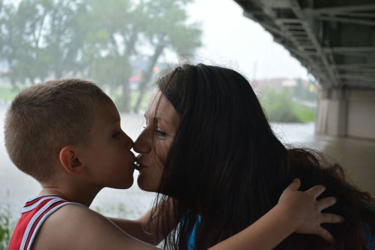 Mother and son kissing during rainy season