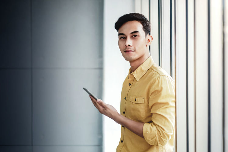 Portrait of Happy Businessman Standing by the Window in Office. Using Smartphone and Smiling. Looking at Camera One Person Young Adult Wireless Technology Standing Young Men Technology Looking At Camera Waist Up Communication Indoors  Connection Mobile Phone Portrait Holding Side View Clothing Wall - Building Feature Leaning Looking At Camera Office Window Smart Smart Phone