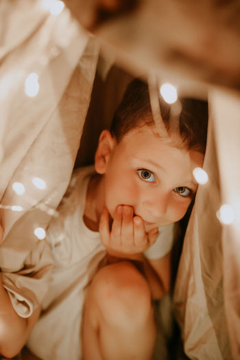 Cute preschool boy in white t-shirt inside shelter made of crumpled sheets with garlands and lights