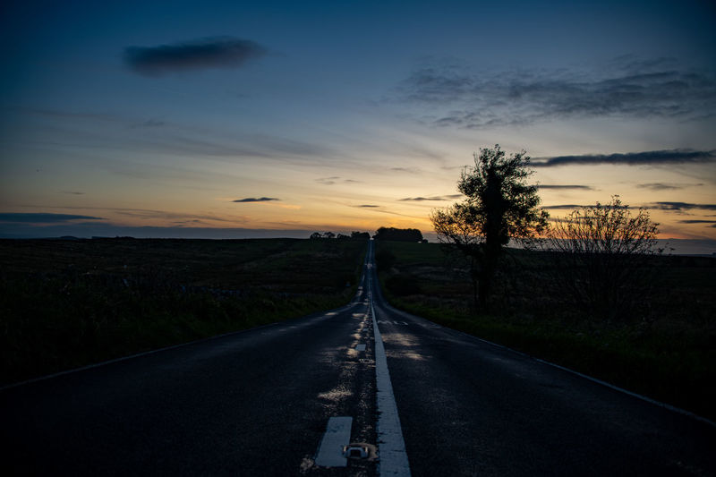 Empty road along landscape at sunset